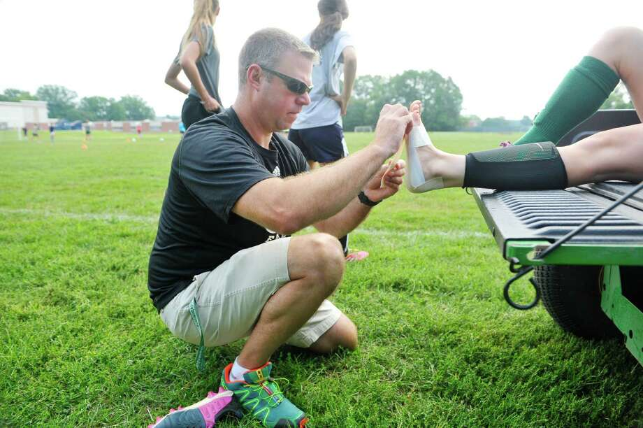 Rick Knizek, athletic trainer at Shenendehowa High School works with girl soccer players at practice on Wednesday, Aug. 19, 2015, in Clifton Park, N.Y.  (Paul Buckowski / Times Union) Photo: PAUL BUCKOWSKI / 00033042A
