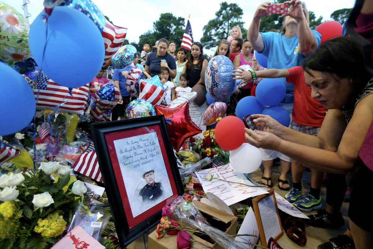 The community pays respect at a vigil in memory of Harris County Sheriff Deputy Darren Goforth after a Prayer March at the Chevron gas station, where he was killed, Sunday, Aug. 30, 2015, in Houston, Texas. Deputy Goforth was killed at a Cypress gas station on Telge and West Road where a vigil is held in his memory.