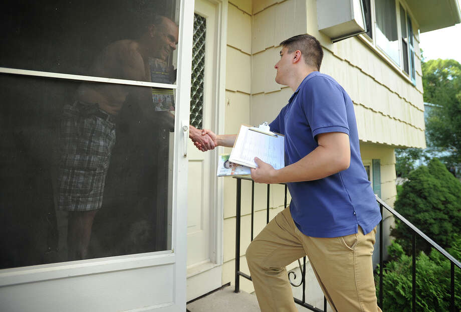 First selectman candidate Zani Imetovski, 23, greets a Seymour resident while going door to door to campaign and introduce himself to voters on Sunday. Below, one of Imetovski's campaign cards sits tucked into a door at a Seymour home after the candidate's visit. Photo: Brian A. Pounds / Hearst Connecticut Media / Connecticut Post
