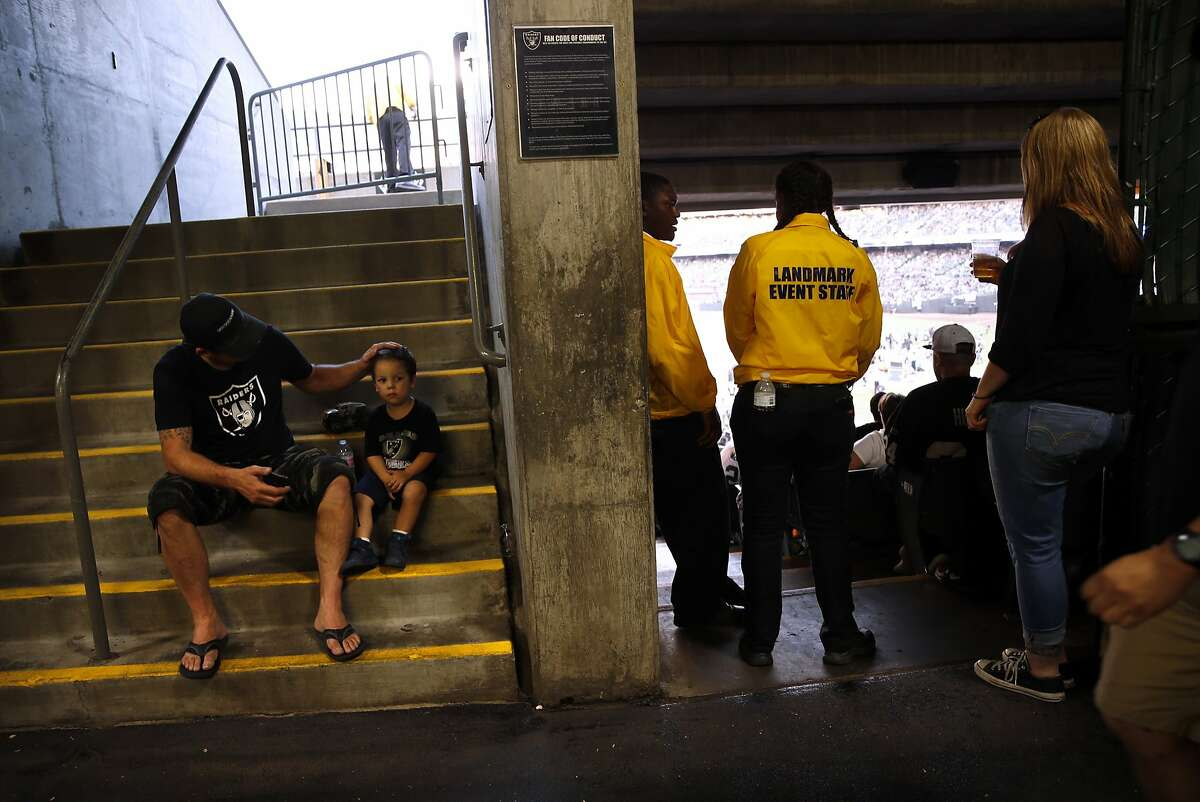 Matt Crim of Walnut Creek and his son Jesse, 2, take a break from the action during Oakland Raiders' preseason game at O.co Coliseum in Oakland, Calif., on Sunday, Aug. 30, 2015.