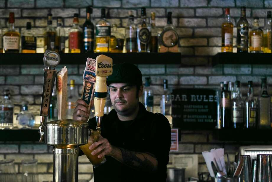 Bartender CJ Frieboes pours a beer from the tap at the Square in San Francisco. Photo: Jen Fedrizzi, Special To The Chronicle