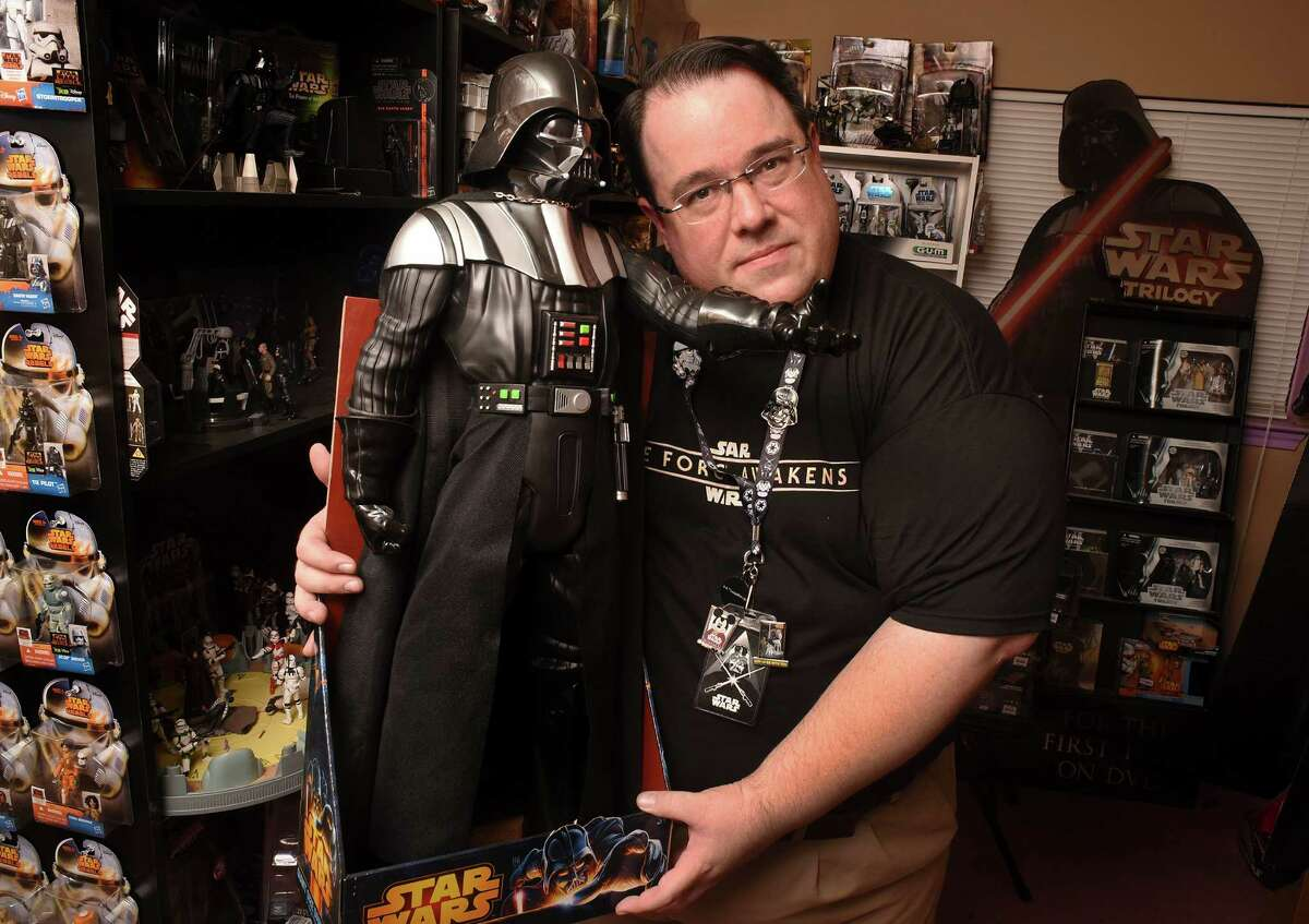 Brian Donahoe holds a 31-inch Darth Vader figure that was given to him by friend Linda Corpus. It is one of his favorite figures from among his vast personal Star Wars collection. The avid Star Wars fan plans to add to his many action figures and other wares when