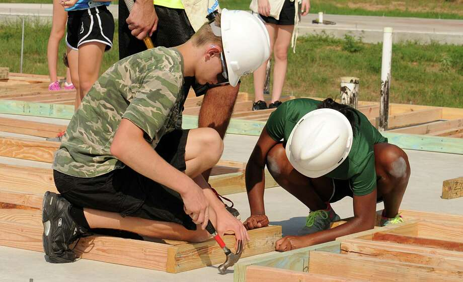 "Anton Matthews and Tayloe Ellis closely examine one of the walls they are building during the John Cooper School Habitat for Humanity house ""Small Walls"" building day in the Cedar Creek neighborhood in Conroe. This will be the 17th Habitat for Humanity house the Cooper School has built. Photograph by David Hopper. Photo: David Hopper, Freelance / freelance"