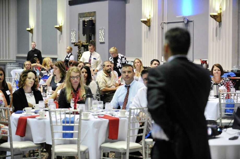 Superintendent Larry Spring, foreground, addresses those gathered during a breakfast and morning program to welcome more than 100 new teachers and administrators to the Schenectady School District at Key Hall at Proctors on Monday, August 31, 2015, in Schenectady, N.Y.   In past years new hires would be around 30 people due to retirements.  Superintendent Larry Spring said that this year's school budget was the first one in years where they were able to increase the budget by 2.5 million instead of cutting the budget like previous years.  (Paul Buckowski / Times Union) Photo: PAUL BUCKOWSKI / 00033175A