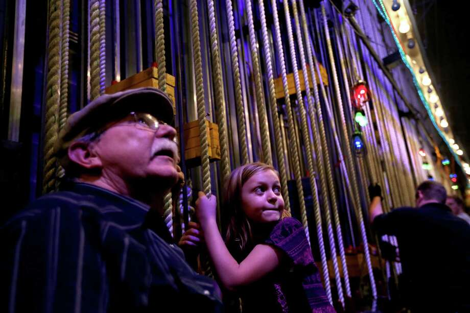 Mike Grawl, house carpenter, instructs Shelby Murchison, 9, of Tomball, to raise a 150-pound curtain along one of the ninety-seven counter weight line sets used for lowering and raising scenery back stage in the Brown Theater at the Wortham Theater Center during the 22nd Annual TransCanada Theater District Open House Sunday, Aug. 30, 2015, in Houston. This annual event marks the kick-off of the Fall performing arts season in Houston, and is a one-day-only opportunity to experience the energy and excitement of Houston's Theater District. Photo: Gary Coronado, Houston Chronicle / © 2015 Houston Chronicle