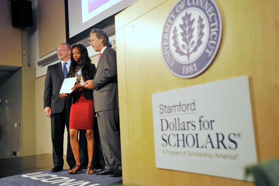 Asia Currie, center, is awarded a scholarship by Stamford Dollars for Scholars co-presidents Jim McClafferty, left, and Tony D'Amelio during the organization's third annual scholarships awards ceremony last year. The group will hold its fourth annual golf tournament fundraiser on Sept. 21. Photo: Jason Rearick / Hearst Connecticut Media / Stamford Advocate