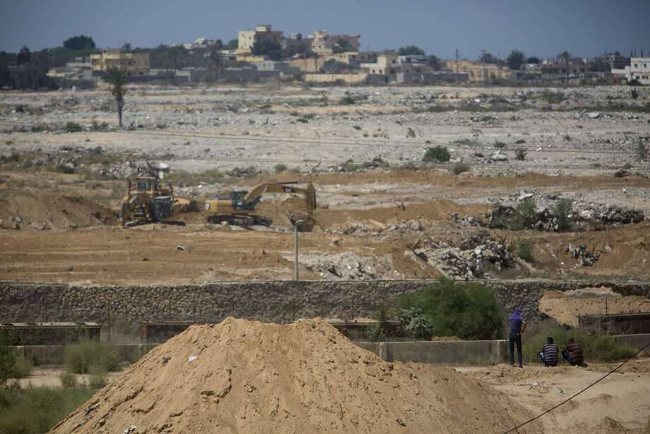 Palestinians watch bulldozers on the Egyptian side of the border with the Gaza Strip. Egypt is seeking to pressure Gaza's Hamas rulers and stamp out militant activity along the border. Photo: Khalil Hamra, Associated Press