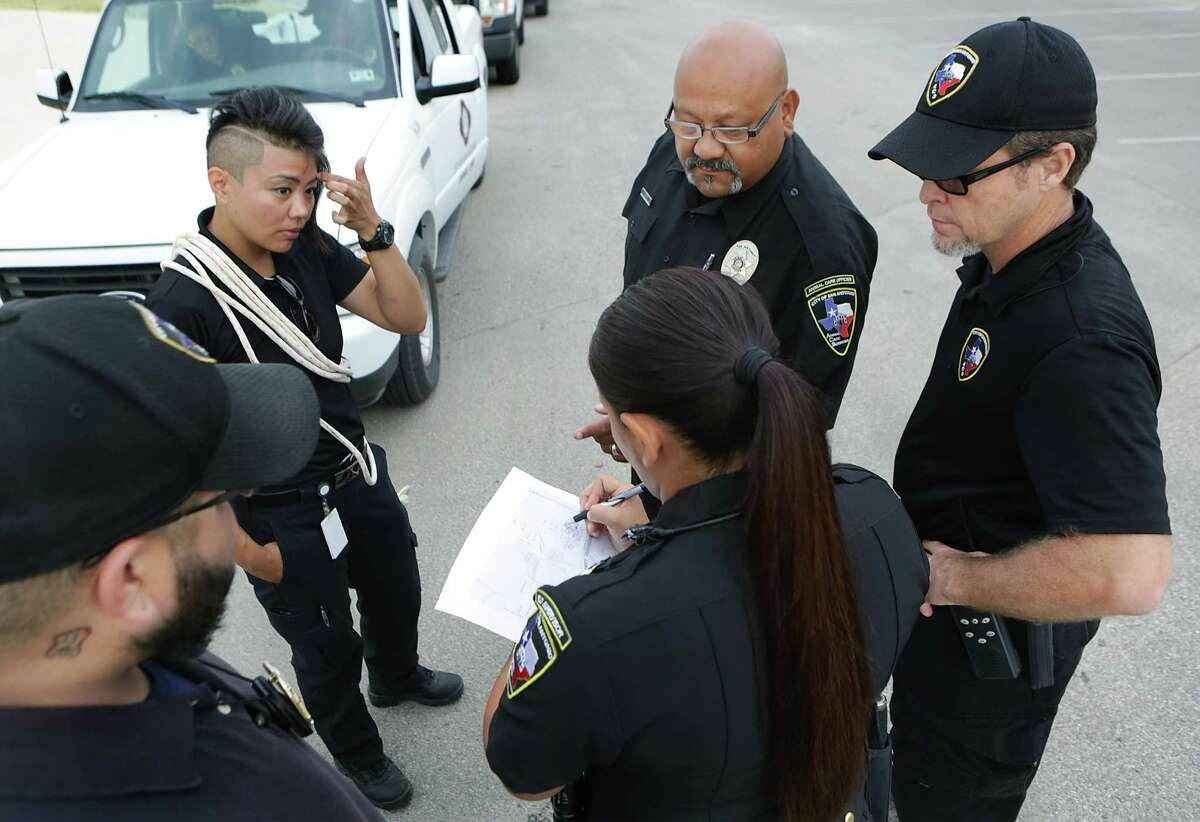 Animal Care Services Field Supervisor Aimee DeContreras, center, goes over location assignments with officers Joseph Flores, from left, Bernadette Obregon, Mike Solis and Field Operation Manager Shannon Sims, right. The officers were block walking on the West Side of San Antonio to distribute flyers in outreach efforts to residents through educational instruction, on Friday, July 31, 2015.