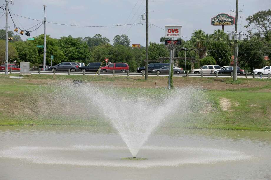 One of two ponds with fountains along West Davis Street near I-45 is shown Friday, Aug. 28, 2015, in Conroe. There are no sidewalks along West Davis Street from the ponds to downtown or the fast-food outlets and pharmacies in between. Photo: Melissa Phillip, Houston Chronicle / © 2015 Houston Chronicle