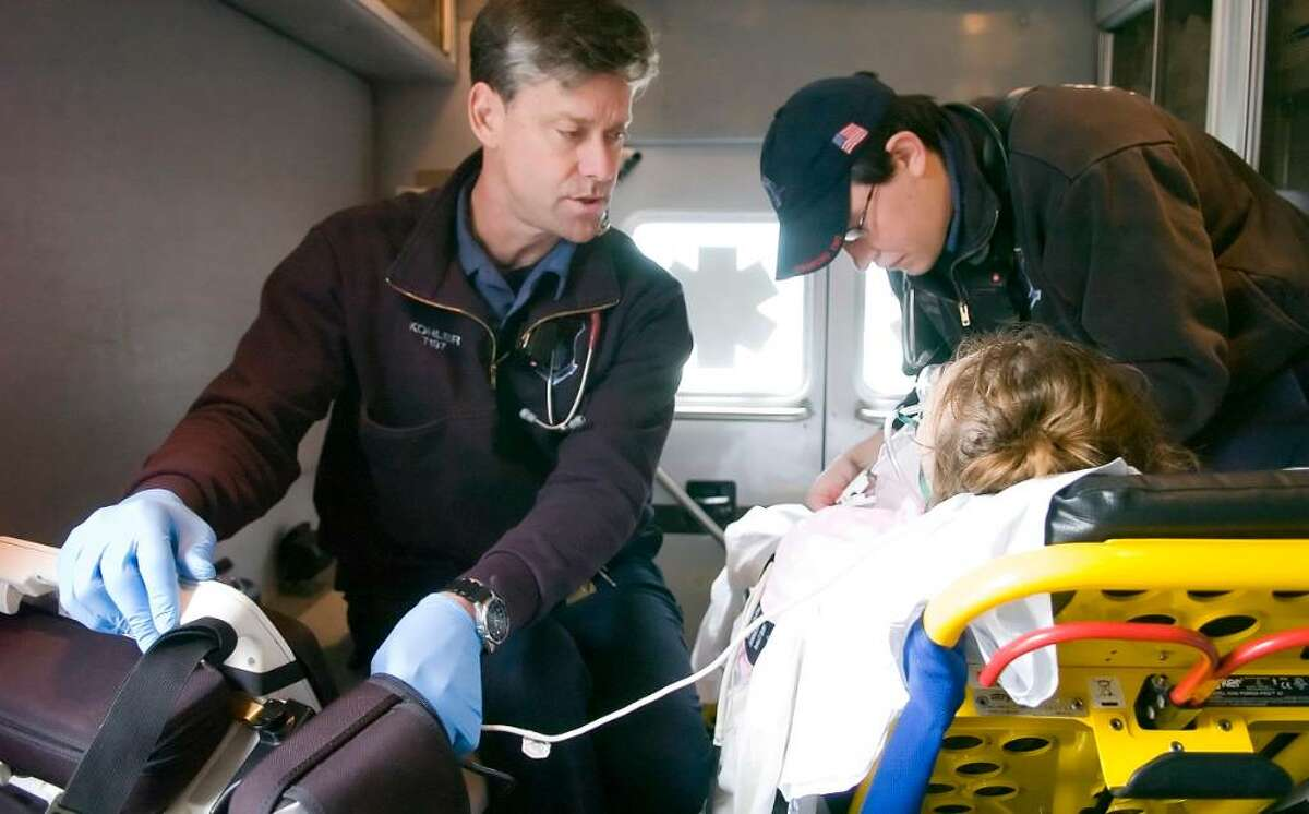 SEMS Paramedic Bob Kohler, left, and EMT Dashell Anderson, right, of work on a patient in the ambulance in Stamford, Conn. on Thursday, March 11, 2010.