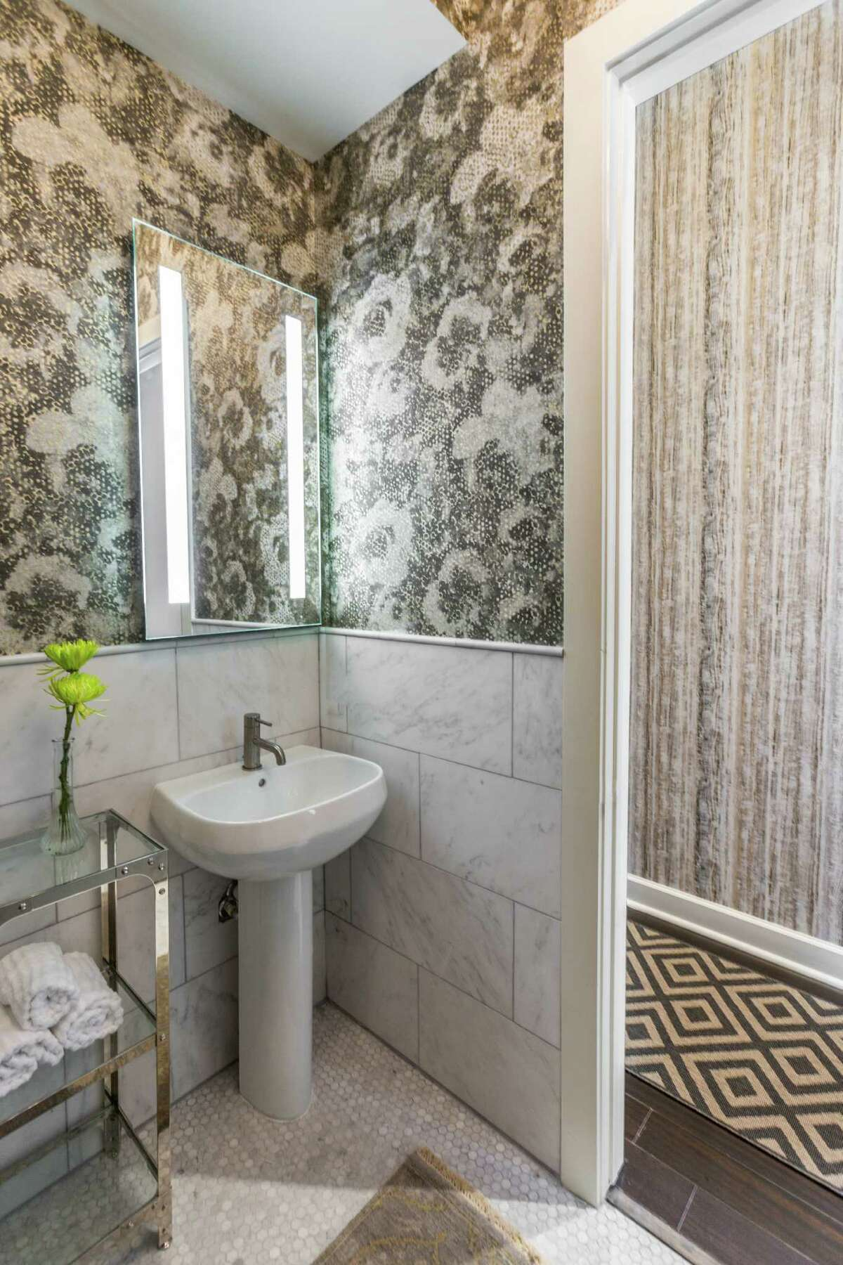 Designer Laura Umansky used a metallic floral-print wallpaper for this powder room in a Heights mid-rise. The metallic tones fit the industrial feel of the condo, but the floral print softens the look.
