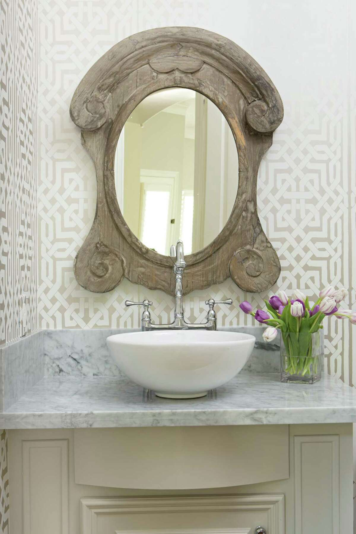 This powder room in The Woodlands is light and bright, but designer Amanda Eck chose a bold wallpaper to add rich texture to the small space.