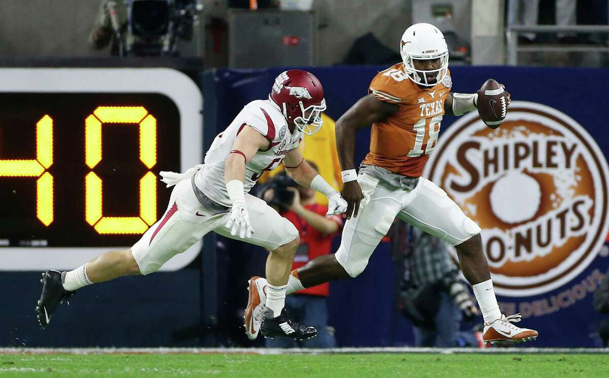 Texas and Arkansas last met in the 2014 Texas Bowl, where the Razorbacks rolled to a 31-7 win. Pictured above, Texas QB Tyrone Swoopes runs to avoid the tackle of Arkansas linebacker Brooks Ellis during the first quarter of the Texas Bowl at NRG Stadium on Dec. 29, 2014, in Houston.