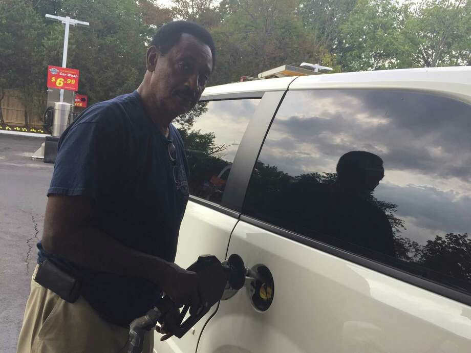 Clarence Bates pumps gas at the Shell station on West Putnam Avenue in Old Greenwich on Aug. 31, 2015. Gas prices are dropping, even though the Labor Day weekend is approaching. Photo: Silvia Foster-Frau / Hearst Connecticut Media / Greenwich Time