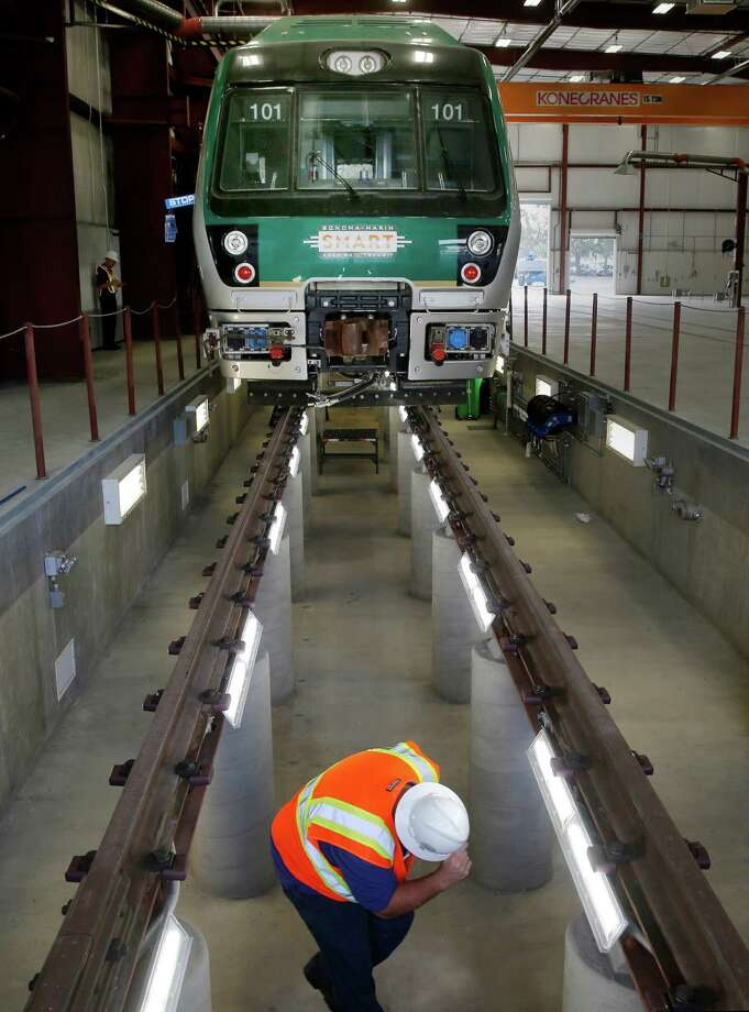 A SMART employee ducks under the tracks in the service bay of the new SMART maintenance yard. Photo: Brant Ward / The Chronicle / ONLINE_YES