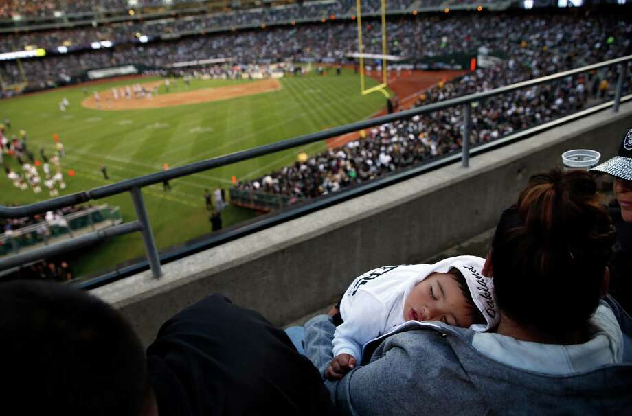 Young Raiders' fan Julian Sabala, 18 months, sleeps during Raiders' preseason game at O.co Coliseum in Oakland, Calif., on Sunday, Aug. 30, 2015. Photo: Scott Strazzante / The Chronicle / ONLINE_YES