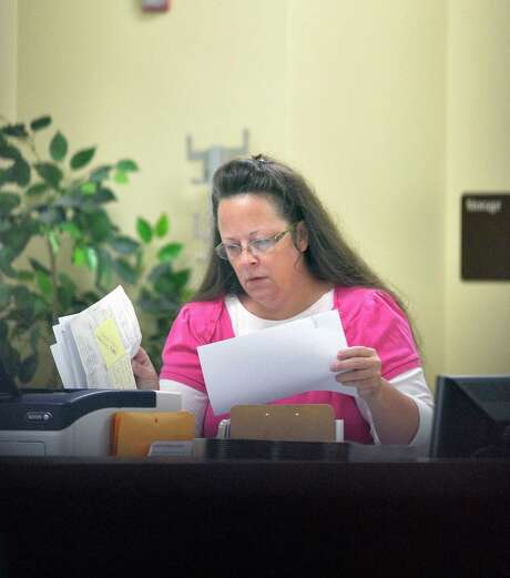 Rowan County Clerk Kim Davis has been sued by four couples after refusing to issue them marriage licenses. The licenses issued since have been altered so they do not include her name.  while her case is under appeal. U.S. District Judge David Bunning denied Rowan County Clerk Kim Davis' request to delay his ruling from last week ordering her to issue marriage licenses to gay and lesbian couples. That ruling followed the U.S. Supreme Court's decision in June legalizing same-sex marriage nationwide. But Bunning then delayed his own decision, effectively granting Davis' request while also denying it. (AP Photo/Timothy D. Easley) Photo: Timothy D. Easley, FRE / FR43398 AP