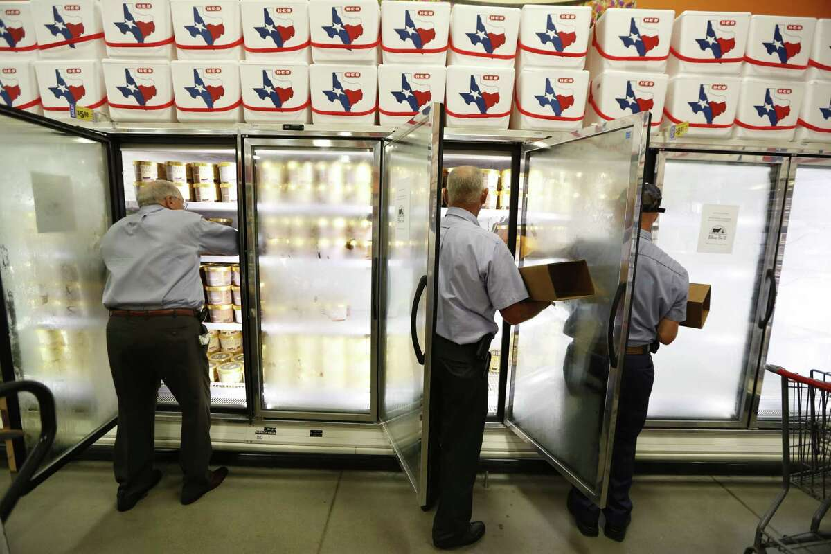 Blue Bell workers Freddie Hugo, from left, Rickey Seilheimer and Charlie Franke stock H-E-B freezers with half gallons of Blue Bell before 6 a.m. on Monday in Brenham.