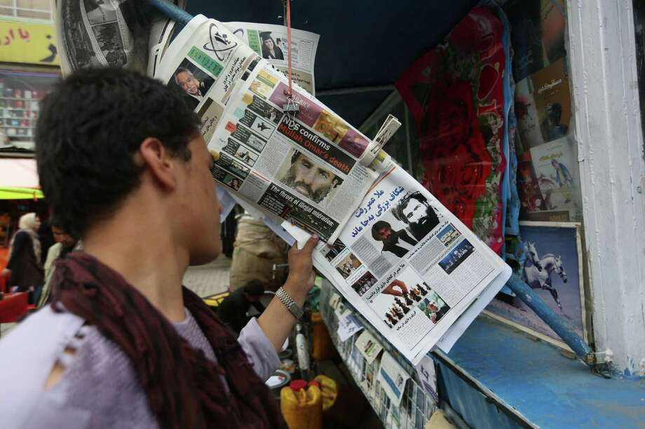 FILE - In this Aug. 1, 2015 file photo, an Afghan reads local newspapers carrying headlines about the new leader of the Afghan Taliban, Mullah Akhtar Mansoor, and former leader Mullah Mohammad Omar who was declared dead, on display at a newsstand in Kabul, Afghanistan. Defying the fury of Afghanistan's government and warnings from Washington, Pakistani authorities appear to be turning a blind eye to a meeting of hundreds of Taliban followers in Quetta, Pakistan, near the Afghan border, aimed at resolving a dispute over the group's leadership following the announcement of the death of one-eyed figurehead Mullah Mohammad Omar. (AP Photo/Rahmat Gul, File) ORG XMIT: CAITH102 Photo: Rahmat Gul / AP