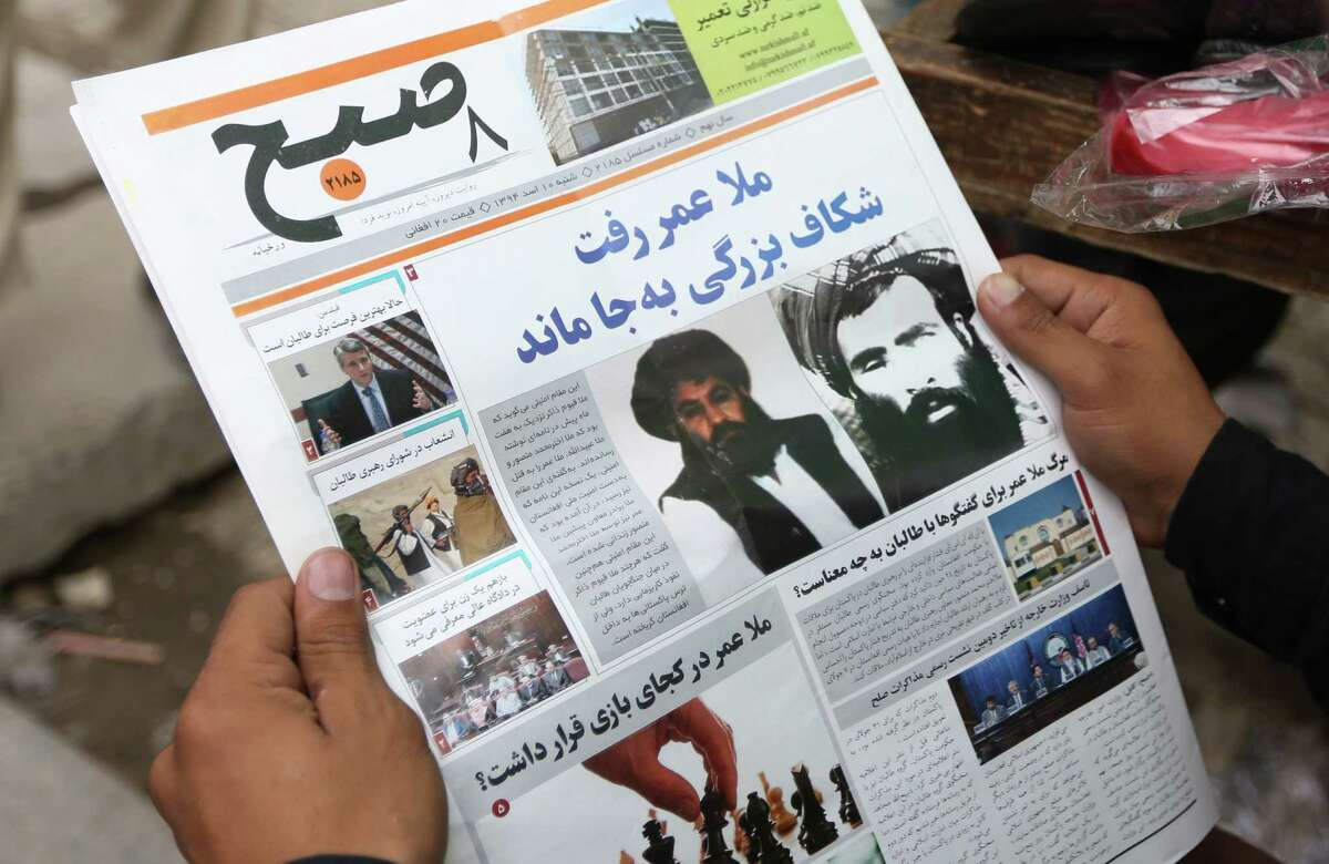FILE - In this Saturday, Aug. 1, 2015 file photo, an Afghan man reads a local newspaper with photos of the new leader of the Afghan Taliban, Mullah Akhtar Mansoor, center, and former leader Mullah Mohammad Omar who was declared dead, in Kabul, Afghanistan. Defying the fury of Afghanistan?'s government and warnings from Washington, Pakistani authorities appear to be turning a blind eye to a meeting of hundreds of Taliban followers in Quetta, Pakistan, near the Afghan border, aimed at resolving a dispute over the group?'s leadership following the death of one-eyed figurehead Mullah Mohammad Omar. (AP Photo/Rahmat Gul, File)