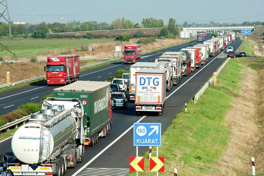 A long queue of vehicles  waits  on the M1 motorway near the border between Hungary and Austria near Mosonmagyarovar, 158 km northwest from Budapest, Hungary, Monday, Aug. 31, 2015. The line has reached 20 kilometers as every vehicle capable of smuggling people is checked  at the border after 71 migrants were found dead in a truck Thursday.   (Csaba Krizsan/MTI via AP) ORG XMIT: MTI204 Photo: Csaba Krizsan / MTI