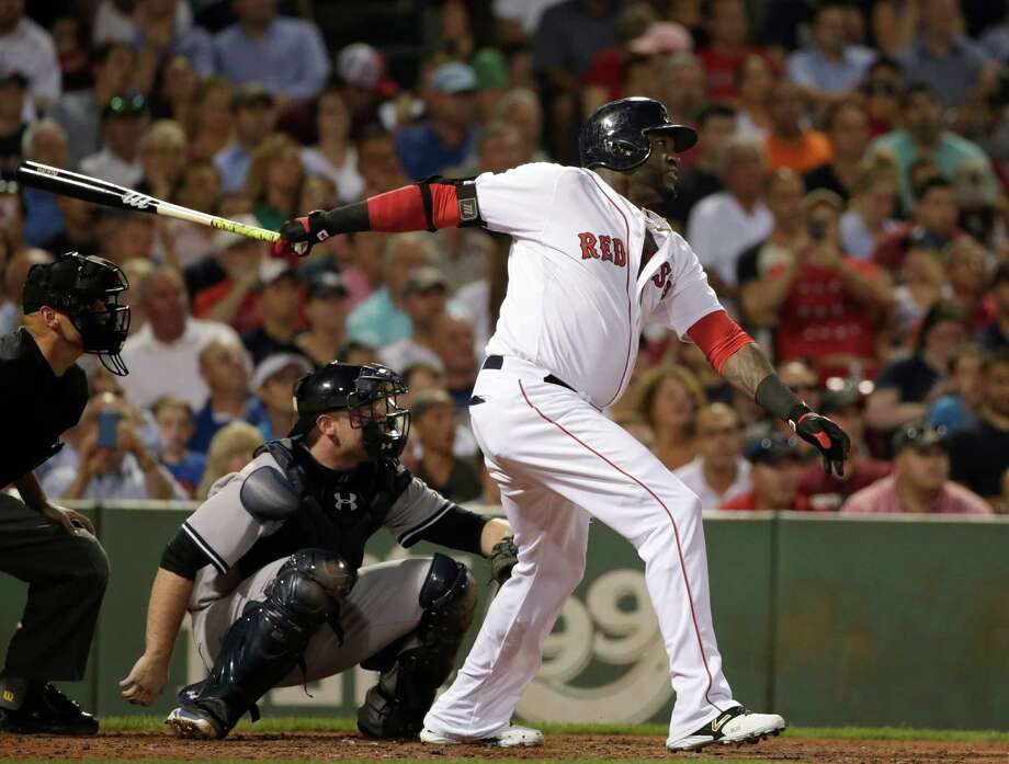 Boston Red Sox designated hitter David Ortiz, right, follows through on his swing as he hits a home run while New York Yankees catcher Brian McCann, left, looks on in the fourth inning of a baseball game, Monday, Aug. 31, 2015, at Fenway Park, in Boston. (AP Photo/Steven Senne) ORG XMIT: MASR110 Photo: Steven Senne / AP