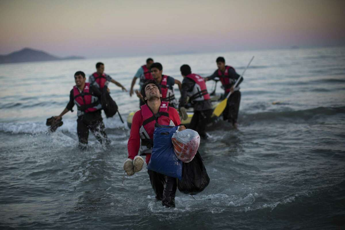 KOS, GREECE - AUGUST 31: Migrants from Pakistan land on shore after completing a journey in a small dinghy crossing a three mile stretch of the Aegean Sea from Turkey August 31, 2015 in Kos, Greece. Migrants from many parts of the Middle East and African nations continue to flood into Europe before heading from Athens, north to the Macedonian border. Since the beginning of 2015 the number of migrants using the so-called 'Balkans route' has exploded with migrants arriving in Greece from Turkey and then travelling on through Macedonia and Serbia before entering the EU via Hungary. The number of people leaving their homes in war torn countries such as Syria, marks the largest migration of people since World War II. (Photo by Dan Kitwood/Getty Images) *** BESTPIX ***