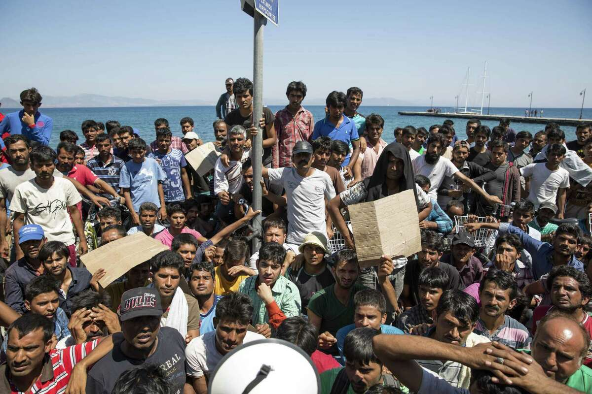 KOS, GREECE - AUGUST 31: A group of Pakistani migrants protest at their lack of progress obtaining transit papers on August 31, 2015 in Kos, Greece. Migrants from many parts of the Middle East and African nations continue to flood into Europe before heading from Athens, north to the Macedonian border. Since the beginning of 2015 the number of migrants using the so-called 'Balkans route' has exploded with migrants arriving in Greece from Turkey and then travelling on through Macedonia and Serbia before entering the EU via Hungary. The number of people leaving their homes in war torn countries such as Syria, marks the largest migration of people since World War II. (Photo by Dan Kitwood/Getty Images)