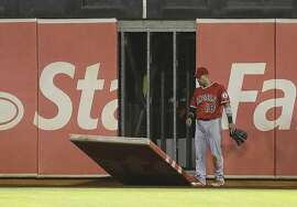 A piece of the left field wall falls as Los Angeles Angels' Shane Victorino watches  in the fifth inning of a baseball game against the Oakland Athletics Monday, Aug. 31, 2015, in Oakland, Calif. Victorino hit the wall trying to field a ball hit by A's Danny Valencia. (AP Photo/Ben Margot)