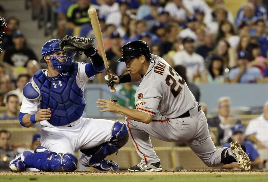 San Francisco Giants' Nori Aoki, right, gets out of the way of a pitch as Los Angeles Dodgers catcher Yasmani Grandal makes the catch during the third inning of a baseball game in Los Angeles, Monday, Aug. 31, 2015. (AP Photo/Chris Carlson) Photo: Chris Carlson, Associated Press
