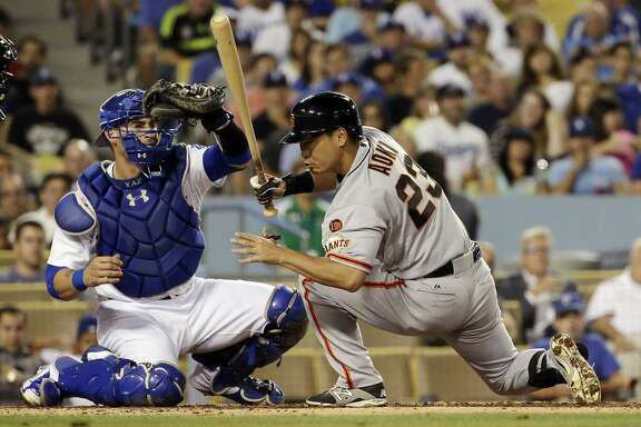 San Francisco Giants' Nori Aoki, right, gets out of the way of a pitch as Los Angeles Dodgers catcher Yasmani Grandal makes the catch during the third inning of a baseball game in Los Angeles, Monday, Aug. 31, 2015. (AP Photo/Chris Carlson)