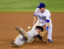 LOS ANGELES, CA - AUGUST 31:  Gregor Blanco #7 of the San Francisco Giants steals second base in front of Chase Utley #26 of the Los Angeles Dodgers during the ninth inning at Dodger Stadium on August 31, 2015 in Los Angeles, California.  (Photo by Harry How/Getty Images)