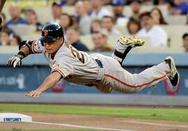 LOS ANGELES, CA - AUGUST 31:  Nori Aoki #23 of the San Francisco Giants dives to first base during the first inning against the Los Angeles Dodgers at Dodger Stadium on August 31, 2015 in Los Angeles, California.  Aoki was out on the play.  (Photo by Harry How/Getty Images)