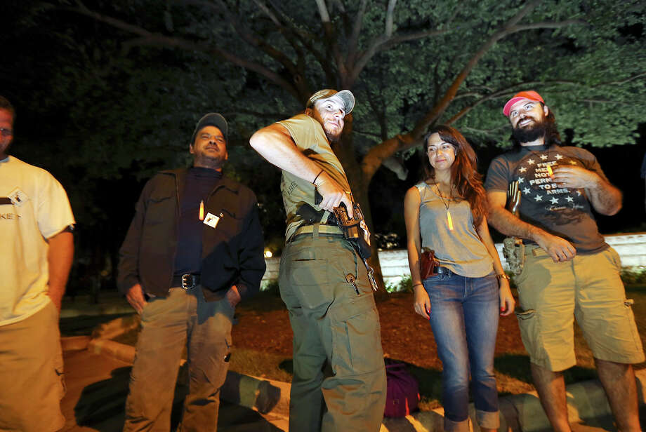 Gun rights activist Crash Turner (center) and others pass around a Smith & Wesson M&P .40 while attending the first open carry of modern pistols event hosted by DontComply.com and Come and Take It Texas in front of the Texas Capitol in Austin, Tx. Tuesday Sept. 1, 2015. About 30 people attended the event. Photo: Edward A. Ornelas, San Antonio Express-News / © 2015 San Antonio Express-News