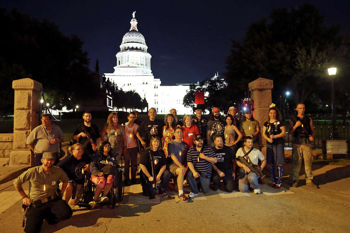 Gun rights activists pose for a photo after marching around the Texas Capitol during the first open carry of modern pistols event hosted by DontComply.com and Come and Take It Texas, Tuesday Sept. 1, 2015 in Austin, Tx. About 30 people attended the event.