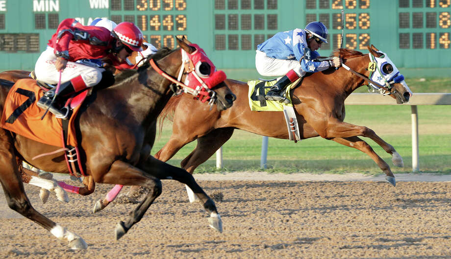 My Moment of Fame (4) , ridden by Luis Ramirez,  jumps out and holds off a challenge by Francisco Calderon on GBH Gunsmoke (7) in the third race during the John Deere Juvenile Challenge Trial at Retama Park  on July 25, 2015. Photo: Tom Reel / San Antonio Express-News