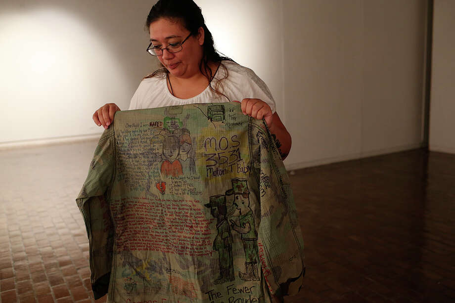 "Regina Vasquez, 36, of San Marcos, holds up her military fatigues that is part of her project, ""Fatigue Clothesline,"" Monday, August 24, 2015. The U.S. Marine served from 1998 to 2002 and was sexually assaulted while she served in the military. Her project consist military fatigues from victims of military sexual trauma. The artwork is part of  ""The Uncertainty of a Life in Security,"" an exhibit at the University of Texas at San Antonio Main Campus art gallery that will open on September 2. Photo: Jerry Lara /San Antonio Express-News / © 2015 San Antonio Express-News"