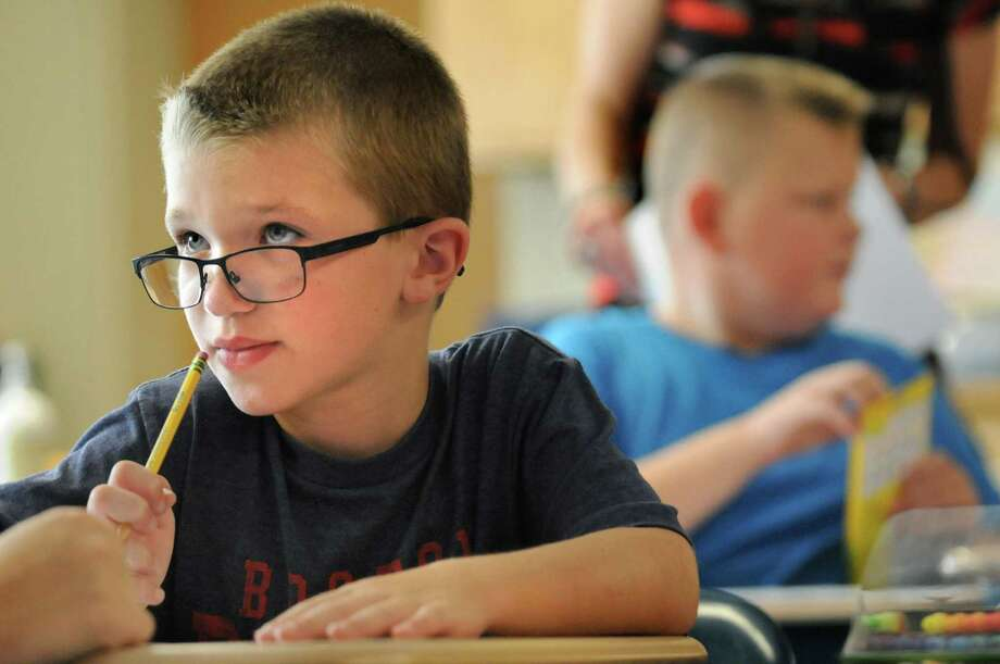 Third-grader James Pazro, 7, left, concentrates on a math activity on the first day of school on Tuesday, Sept. 1, 2015, at Glencliff Elementary in Rexford , N.Y. (Cindy Schultz / Times Union) Photo: Cindy Schultz / 00033180A