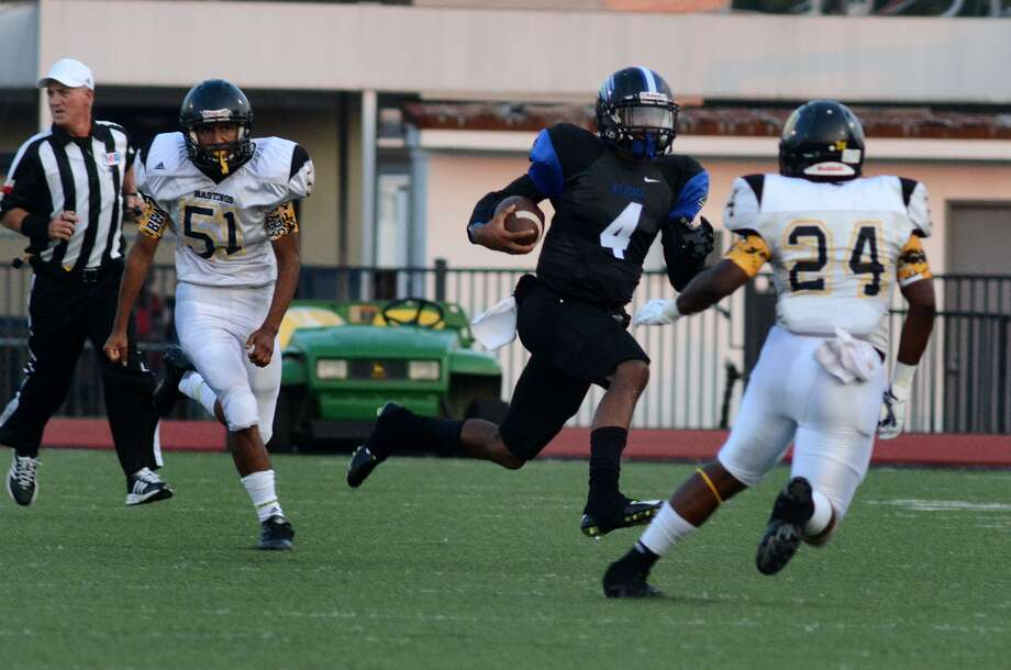 Dekaney senior quarterback Adrian Hardy (4) runs for yardage between Hastings defenders Noah Felix (51) and Cedric Davis Crumpton (24) during their season opener at Leonard George Stadium last week. Photo: Jerry Baker, Freelance