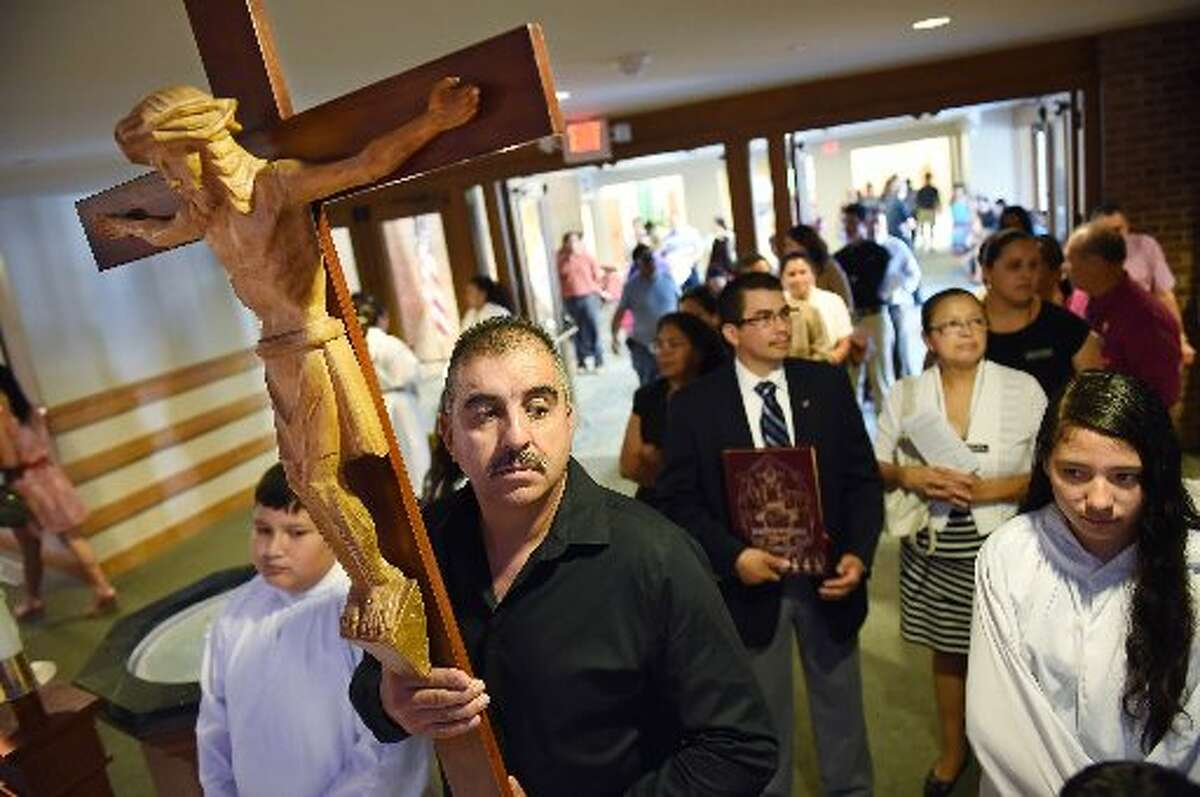 Isaias Castro holds a cross as he and others prepare for a procession at the beginning of a Spanish Mass at Good Shepherd Catholic Church in Alexandria, Va.