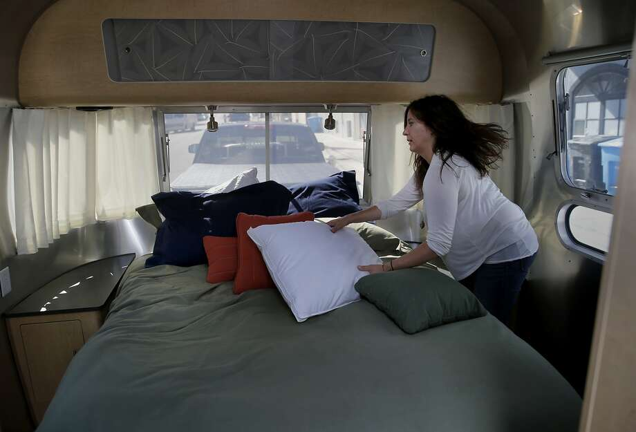 Jen Young makes some finishing touches on the large master bedroom in the Airstream Monday August 31, 2015. Jeff Cavins and Jen Young, the couple who started Outdoorsy, an Airbnb for RV's and trailers, moved furniture from their North Beach apartment to their Airstream trailer to begin living the RV lifestyle. Photo: Brant Ward, The Chronicle