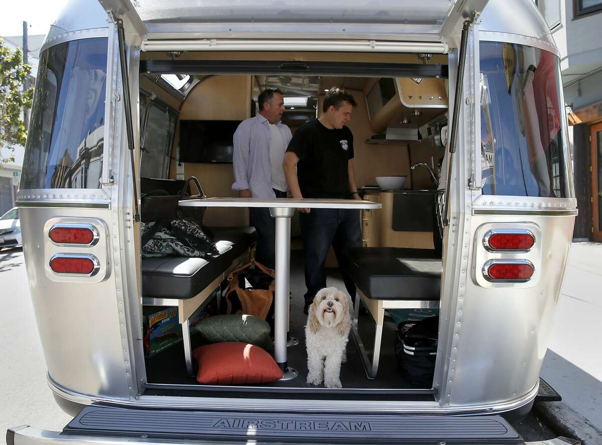 Lucy Chew, the family dog, checks out the rear of the new Airstream while Jeff Cavins and associate Ryan Quinn load the trailer Monday August 31, 2015. Jeff Cavins and Jen Young, the couple who started Outdoorsy, an Airbnb for RV's and trailers, were moving furniture from their North Beach apartment to their Airstream trailer to begin living the RV lifestyle.