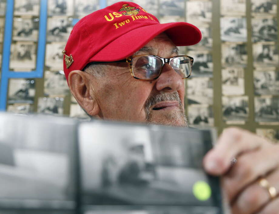 "In this Wednesday, Aug. 12, 2015, photo, World War II veteran Francis ""Dick"" Varone poses with a portrait of himself that was taken in a Mechanicville tavern during the war, at the Mechanicville Public Library in Mechanicville, N.Y. Seventy years after the war officially ended with Japan's surrender on Sept. 2, 1945, Siciliano's Restaurant in Mechanicville is long gone, but the black-and-white portraits endure. (AP Photo/Mike Groll)"