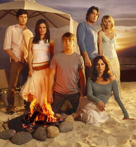 "The cast of Fox's ""The O.C."" in 2006. The show aired from 2003-2007. Here's a publicity shot of Adam Brody as Seth, Rachel Bilson as Summer, Benjamin McKenzie as Ryan, Melinda Clarke as Julie, Peter Gallagher as Sandy, and Kelly Rowan as Kirsten on the beach."