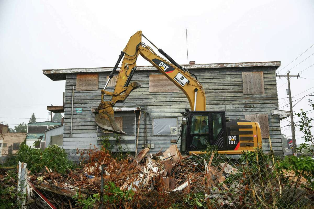 Blighted properties formerly owned by Hugh and Martha Sisley are torn down Tuesday, September 1, 2015 in the Roosevelt neighborhood. Developers and the city intend to turn the properties into affordable housing and public spaces.