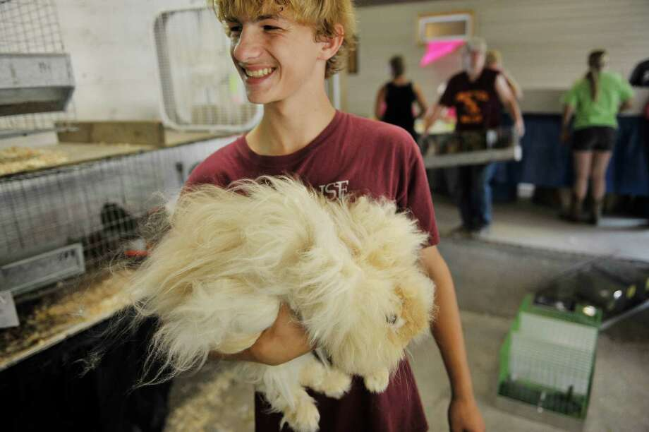 Timothy Mazur, 16, of Amsterdam holds his angora rabbit, Stuffy during opening day at the Fonda Fair on Tuesday, Sept. 1, 2015, in Fonda, N.Y.  Mazur will show Stuffy in the open show class.  (Paul Buckowski / Times Union) Photo: PAUL BUCKOWSKI / 00033165A