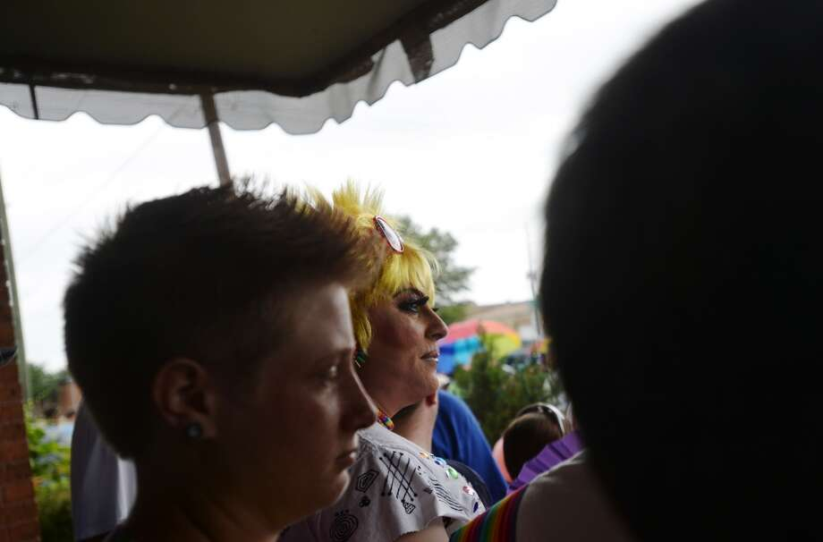Olivia Gardner, center, and others hide from the rain on a porch before Saturday's Pride walk. The second annual Beaumont Pride walk and festival was held Saturday in downtown Beaumont. Participants walked down Broadway to Crockett Street, where more than two dozen vendors were arranged in the parking area. Photo taken Saturday 6/13/15 Jake Daniels/The Enterprise Photo: Jake Daniels/The Enterprise