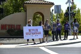 A broad coalition of activists gather in front of Netflix to protest the company's parental leave program in Los Gatos, Calif., on Tuesday, Sept. 1, 2015.
