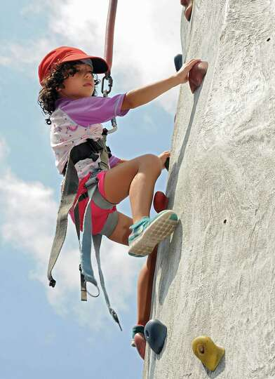 Tia Mukamal, 7, of Ghent, makes her way up the rock climbing wall at FunPlex Fun Park in  East Green