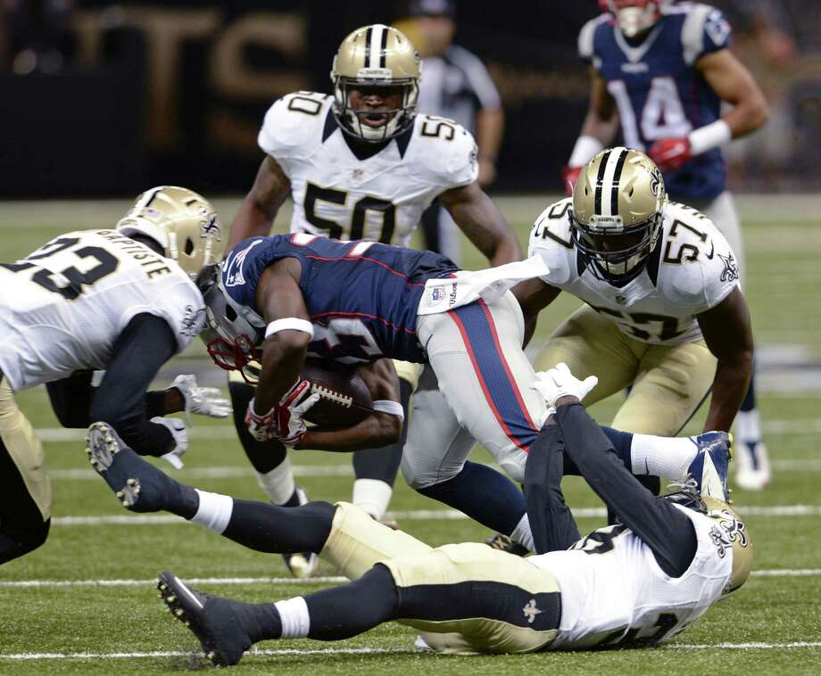 New England Patriots running back Dion Lewis (33) is upended between New Orleans Saints cornerback Stanley Jean-Baptiste (23) and inside linebacker David Hawthorne (57) in the first half of a preseason NFL football game in New Orleans, Saturday, Aug. 22, 2015. (AP Photo/Bill Feig) ORG XMIT: LAGH108 Photo: Bill Feig / FR44286 AP